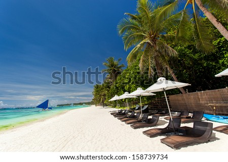 Sun umbrellas and beach chairs on tropical coastline, Philippines, Boracay