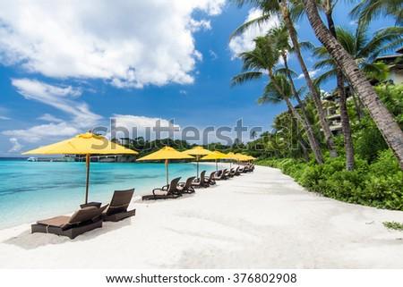 Sun umbrellas and chairs on tropical beach - stock photo