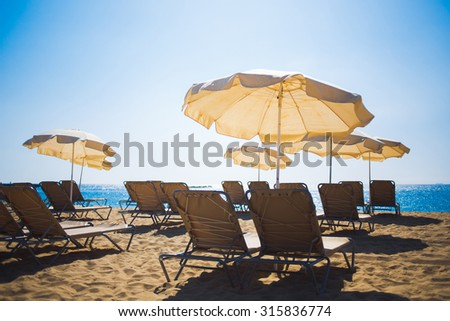 Sun umbrellas and free deck chairs standing on the sandy beach in summer day against blue sky background with copy space area for your text message or advertising content, relax and vacation holidays - stock photo