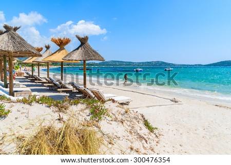 Sun umbrellas on beautiful beach in Saint Cyprien coastal town, Corsica island, France - stock photo