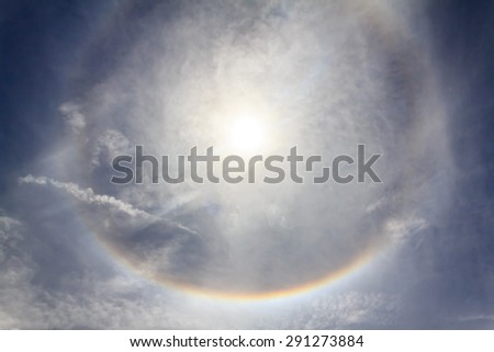 Sun with circular rainbow sun halo in sky with cloud - stock photo