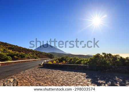 Sun with sunlight over mountains on blue sky with fog and Teide volcano, Tenerife, Canary Islands, Spain - stock photo
