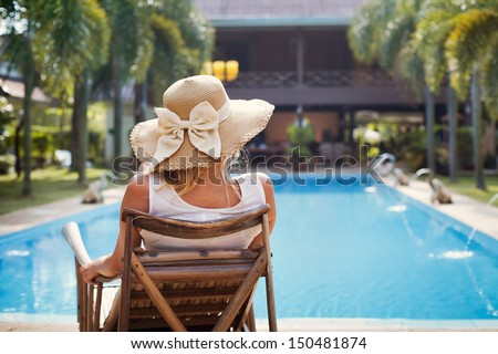 sunbath near swimming pool, fashion woman in hat - stock photo