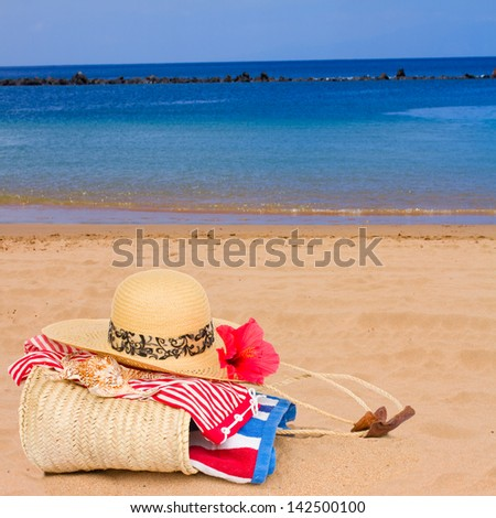 sunbathing accessories on sandy beach by the ocean - stock photo