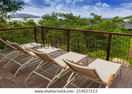 Sunbathing chairs on wooden decking with blue ocean view