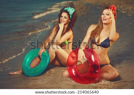 Sunbathing girls wearing  bikini with lifebuoys on beach - stock photo