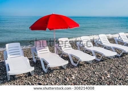 Sunbathing plastic beds and red umbrella on the beach near sea  - stock photo