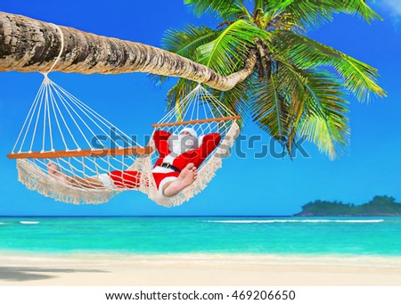 Sunbathing Santa Claus waiting New Year's holidays and relax in cozy mesh hammock in shadow under palm tree at tropical paradise ocean beach in sunny day - christmas vacation in hot countries concept