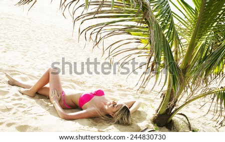 Sunbathing Under Palm blond Caucasian sexy Female with long slim legs  Girl Beautiful full length body woman lie on hot yellow sand Person wearing pink swimsuit or red Two-Piece Bikini on tanned skin  - stock photo