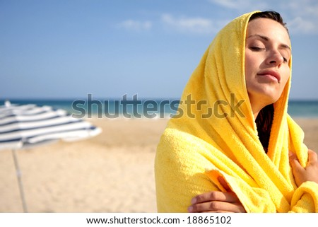 sunbathing woman in yellow towel with coastline in background - stock photo
