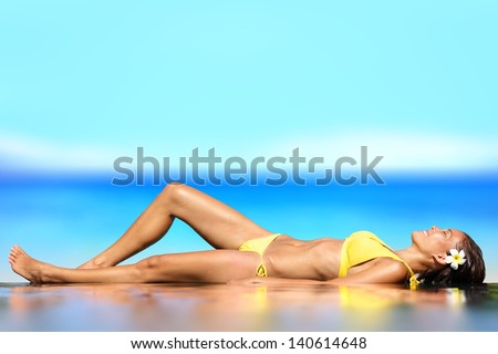 Sunbathing woman relaxing under sun in luxury. Woman lying on her back on wet sand in front of the ocean at the seaside sunbathing in her bikini with a happy smile and a flower in her hair. - stock photo