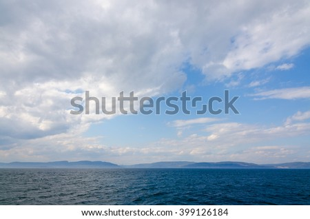 Sunbeam on dark sky above the sail boat on St. Lawrence river - stock photo