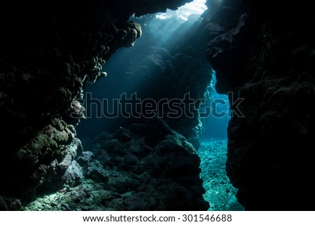 Sunbeams fall into the dim shadows of a cavern in the Solomon Islands. Coral reefs in this Melanesian region are exceedingly diverse. The area also offers great scuba diving and snorkeling. - stock photo