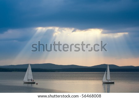 Sunbeams in the cloudy sky with two yachts in the foreground