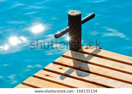 sunbeams on the sea water near the wooden pier - stock photo