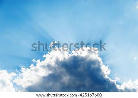 sunbeams over dramatic cloud in blue sky - stock photo