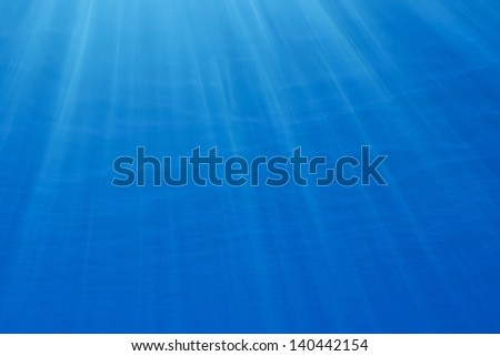 Sunbeams penetrating blue ocean background - stock photo