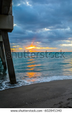 sunbeams reflecting on the ocean and the shells lying on the beach with pilings from a pier