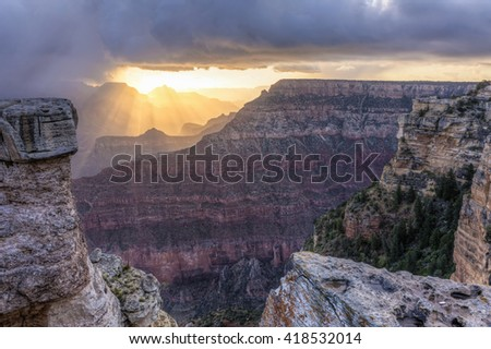 Sunbeams shine through a snow squall over Cedar Ridge and Pattie Butte seen from Mather Point in Grand Canyon National Park, Arizona. - stock photo