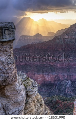 Sunbeams shine through a snow squall over Cedar Ridge and Pattie Butte seen from next to a rock tower off Mather Point in Grand Canyon National Park, Arizona. - stock photo