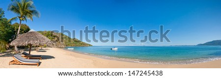 Sunbed and straw umbrella on a beautiful tropical beach - stock photo