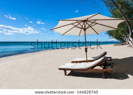 Sunbed and umbrella on a beautiful tropical beach - stock photo