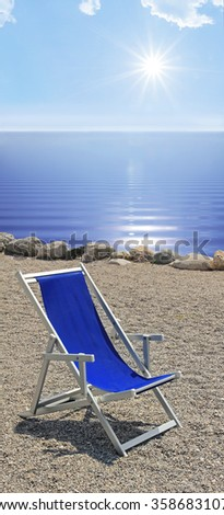 sunbed at the stony beach, blue wavy water and bright sunshine, summer holidays