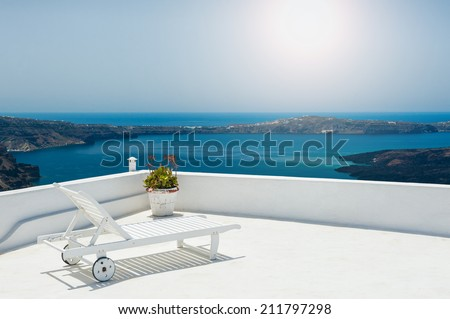 Sunbed on the terrace. White architecture on Santorini island, Greece. Beautiful view on the sea - stock photo