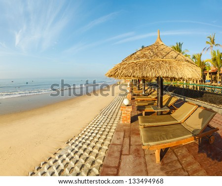 sunbed, umbrellas on background of the sea and sky at dawn - stock photo