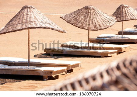Sunbeds and parasols on sandy beach. - stock photo