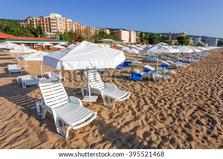 Sunbeds and sun umbrellas on the beach of sea. - stock photo