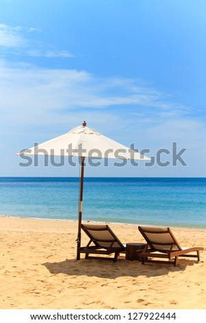 Sunbeds and umbrella on a tropical beach - stock photo