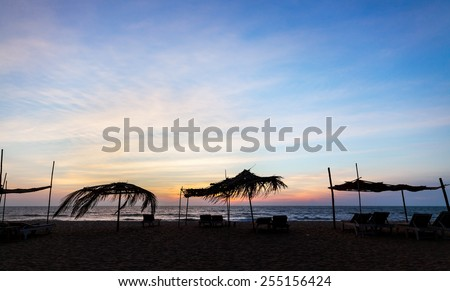 Sunbeds and umbrellas on the beach at sunset - stock photo