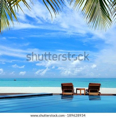 Sunbeds beside swimming pool in maldives beach resorts -- Tropical vacations concept  - stock photo