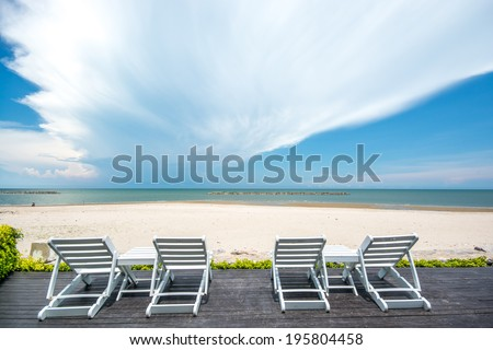 Sunbeds beside swimming pool in Thailand beach resorts. - stock photo