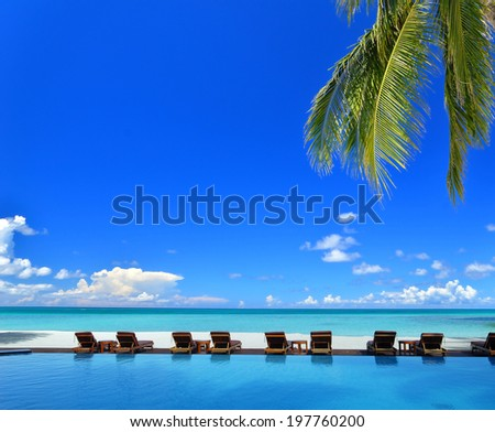 Sunbeds beside swimming pool in tropical beach resorts -- Tropical vacation concept - stock photo