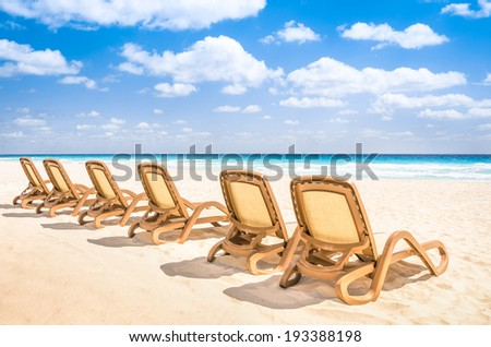 Sunbeds chaise longue at tropical empty beach and turquoise sea - Panorama of dream vacation in exclusive destination with white sand in a sunny beautiful day  - stock photo