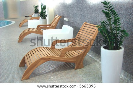 Sunbeds in the fitness near swimming pool with plants