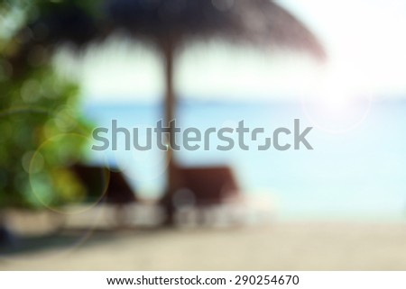 Sunbeds on beautiful beach in resort, blurred texture - stock photo