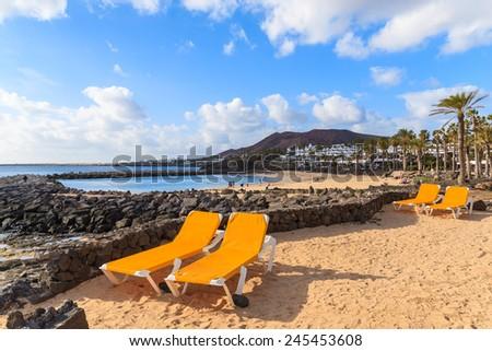 Sunbeds on Playa Blanca volcanic beach, Lanzarote, Canary Islands, Spain  - stock photo