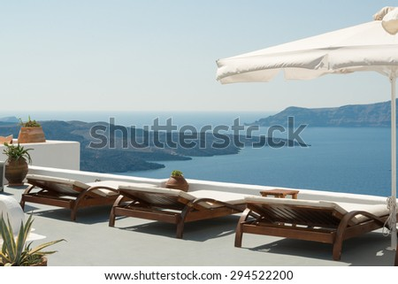 Sunbeds with caldera view on traditional terrace, Santorini - stock photo
