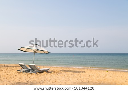 sunbeds with umbrellas on a beautiful sandy beach with clear water  - stock photo