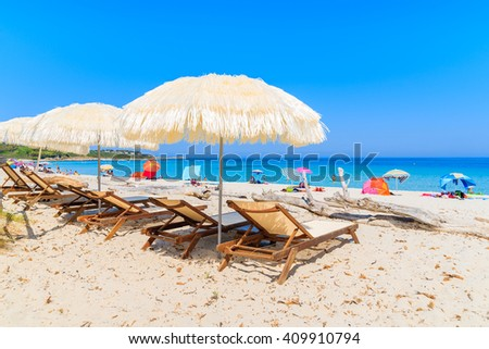 Sunbeds with umbrellas on Bodri beach, Corsica island, France - stock photo