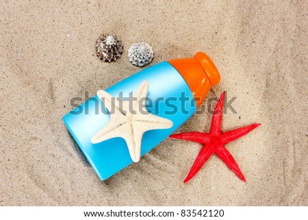 sunblock in bottle, shells and starfish on sand - stock photo