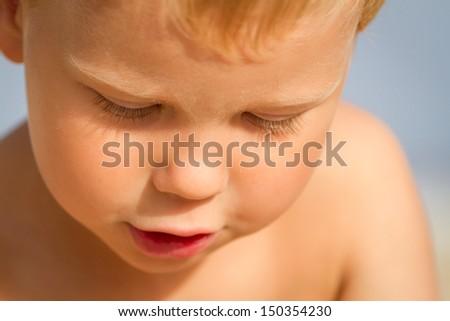Sunburned three year old boy on the beach - stock photo