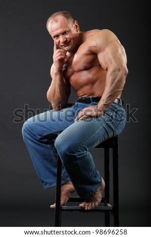 Sunburnt smiling bodybuilder wearing in jeans sits at stool inside black studio - stock photo