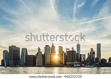 Sunburst between buildings of the Manhattan skyline in New York City during sunset with airplane - stock photo