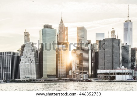 Sunburst between skyscrapers of the Manhattan skyline in New York City during sunset - stock photo