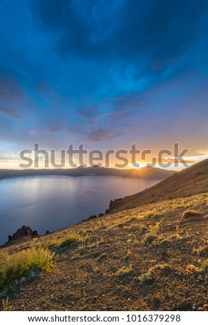 Sunbursts Over The Rim Of Crater Lake in summer afternoon