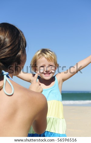 Suncare on the beach: Mother applying suncream to her happy child - stock photo